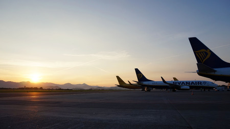 BERGAMO, ITALY - MAY 31, 2017: airplanes on the parking lot and beautiful sunrise on background at Orio al Serio International Airport. Editorial