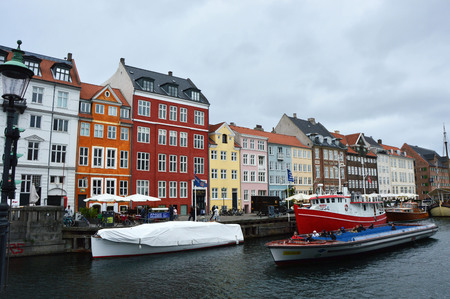 danish: COPENHAGEN, DENMARK - MAY 31, 2017: people in open cafes of the famous Nyhavn promenade. Nyhavn a 17th century harbor in Copenhagen with typical colorful houses and water canals, Copenhagen, Denmark