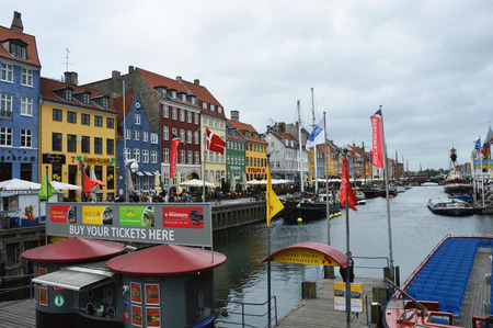COPENHAGEN, DENMARK - MAY 31, 2017: tourists in open cafes of famous Nyhavn promenade. Nyhavn a 17th century harbor in Copenhagen with typical colorful houses and water canals, Copenhagen, Denmark Editorial
