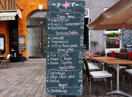 COPENHAGEN, DENMARK - MAY 31, 2017: Blackboard restaurant menu on the Nyhavn canal. Nyhavn is waterfront, canal and entertainment district in Copenhagen. It is lined by colored restaurants and cafes. Editorial