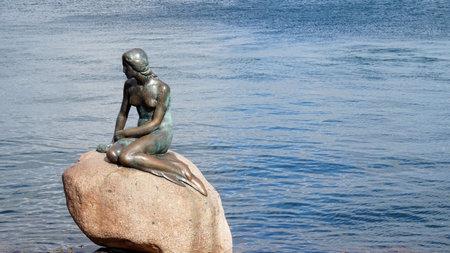 COPENHAGEN, DENMARK - MAY 31, 2017: The bronze statue of the Little Mermaid, Den lille Havfrue, on the coastal rocks by the waterside at the Langelinie promenade in Copenhagen, Denmark