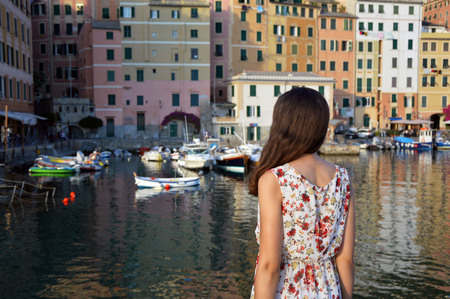 genoa: Back side of beautiful girl looking at Camogli harbor with colorful houses in a typical italian landscape, Italy, Europe