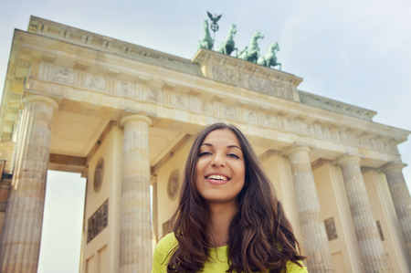 Happy smiling girl in front of Brandenburg Gate, Berlin, Germany. Beautiful young woman travel in Europe.
