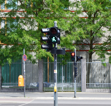 stop and go light: Two traffic lights for pedestrians in Berlin with the characteristic Ampelm?nnchen, the little man at the traffic light, green and red, in Berlin, Germany
