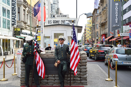 Checkpoint Charlie, famous passage between the West and East Berlin during the Cold War. American soldier standing guard holding the flag.