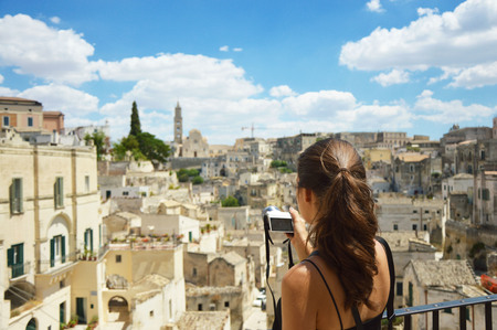 Young woman take photo with mirrorless camera to the old town of Matera. Beautiful girl traveler visit Sassi di Matera. Typical italian landscape. Female in south italian scenary