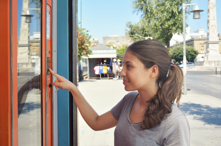 Vending machine. Attractive girl tanned buying drinks in summer. Young student or female tourist choosing a snack or drink at vending machine Archivio Fotografico