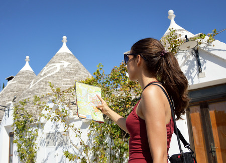 Cheerful woman with sunglasses and long hair searching direction on location map while traveling abroad, happy female tourist searching road to hotel on atlas in a foreign city during vacation Stock Photo