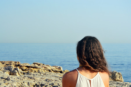 Back view of young woman with curly hair looking at the sea from rocky coast. Traveler on background beach. Stock Photo
