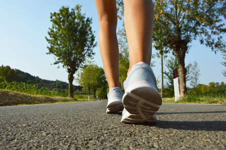 Young fitness woman legs running on asphalt road