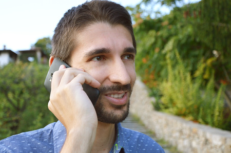 A man is talking on the phone outdoors