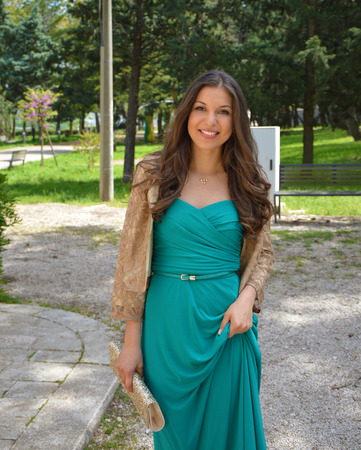 luxurious: Fashion outdoor photo of beautiful smiling young woman with long hair in luxurious green dress posing for the camera