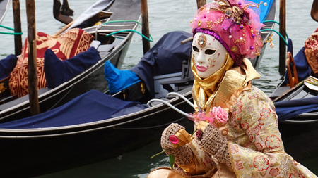 VENICE, ITALY - FEBRUARY 23, 2017: An unidentified masked person in costume during the Carnival of Venice with gondolas on the background