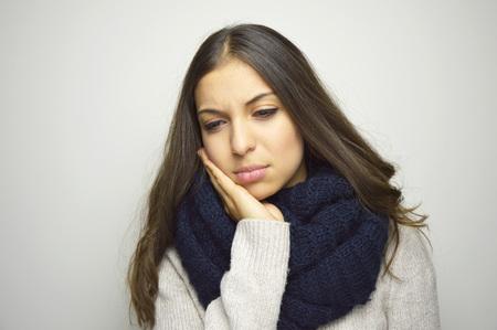 치통을 앓고 있습니다. 회색 배경 서 그녀의 뺨을 만지고 스카프와 함께 아름 다운 젊은 여자.