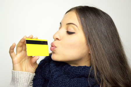 Young fashion woman in love with her credit card isolated on gray background
