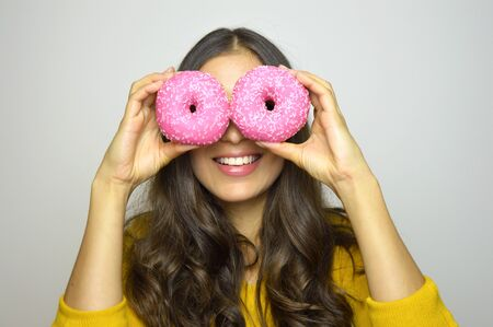 Portrait of smiling girl having fun with sweets isolated on gray background. Attractive young woman with long hair posing with donuts in her hands