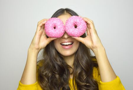 Smiling girl having fun with sweets isolated on gray background. Attractive young woman with long hair posing with donuts in her hands. Banco de Imagens