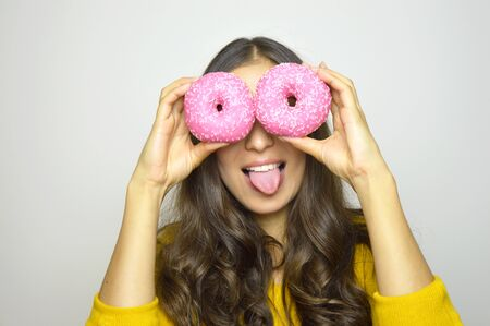 Close-up portrait of funny smiling girl with donuts isolated on gray background. Attractive young woman with long hair posing with sweets in her hands