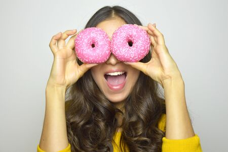 Close-up portrait of long-haired smiling girl having fun with sweets isolated on gray background. Attractive young woman with long hair posing with pink donuts in her hands