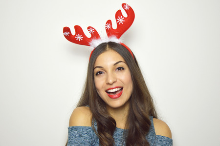 Happy beautiful woman with reindeer horns on her head looks at camera on white background. Christmas holidays.