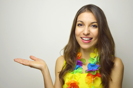 Attractive cheerful girl ready for carnival party showing your product or text on white background. Copy space.