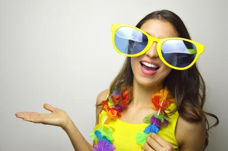 Carnaval tijd. De jonge vrouw met grote grappige zonnebril en Carnaval-slinger glimlacht bij camera en toont uw product of tekst op grijze achtergrond.
