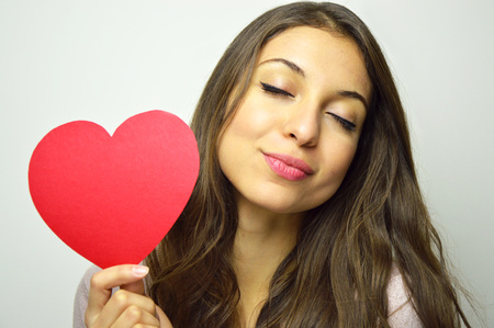 Valentine's Day. Sweet girl in love with closed eyes holding a paper heart and smile at camera on gray background.