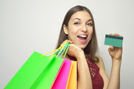 Cheerful excited surprised young woman with credit card and shopper over white background