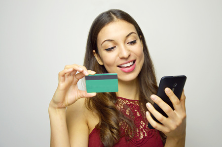 Happy smiling girl holding credit card in hand on white background. E-commerce woman. People doing shopping online.