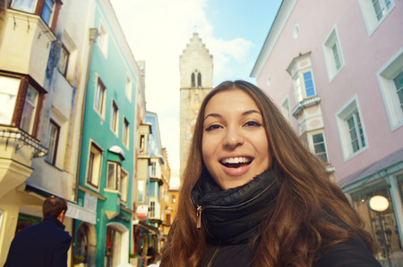 Happy smiling girl in front of Zwölferturm tower in the old town of Sterzing, South Tyrol, Italy. Beautiful young woman winter travel in Europe. Stock Photo