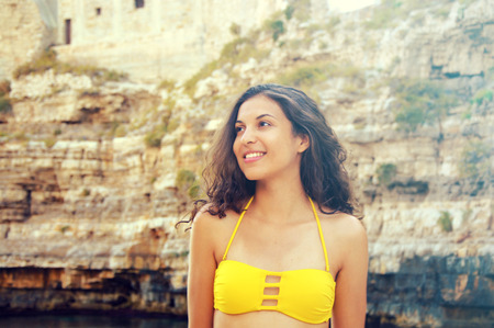 Portrait of young woman with yellow bikini looking to the side. Vintage filter.