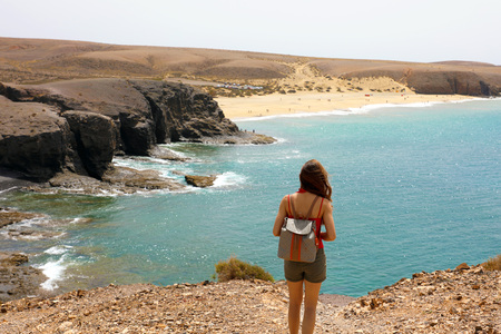 Woman looking to breathtaking panorama of Lanzarote, Canary Islands. Back view of young woman with backpack on the beach.