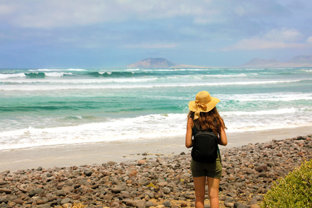 Young female hiker discovering the wild paradisiac beach in Lanzarote Island. Canary Islands, Spain. 免版税图像
