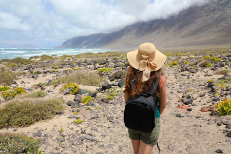 Adventure travel concept. Young woman looking to the fantastic landscape of Lanzarote. Back view of female figure with straw hat.