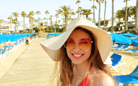 Smiling young woman with straw hat looking at camera. Happy beautiful girl with deck chairs, umbrellas and palm trees, typical tropical scenery at Canary Islands, Spain