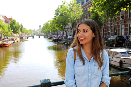 Young beautiful woman fascinated by Amsterdam atmosphere, Netherlands, Europe