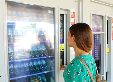 Young female backpacker tourist choosing a snack or drink at vending machine in Venice, Italy. Vending machine with girl. Stockfoto