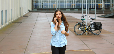 Young doubtfully entrepreneur business woman talking on cell phone outside her office building. Banner crop for copy space.