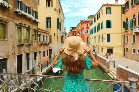 Sweet romantic girl charmed by Venice landscape. Rear view of female tourist on a bridge in Venice, Italy. Imagens
