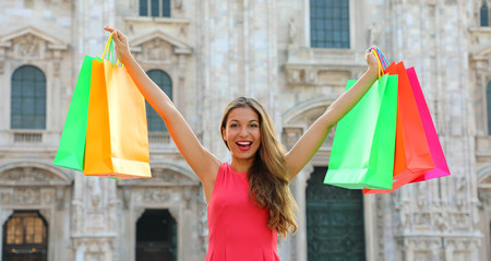 Shopping and tourism concept banner. Euphoric beautiful woman with shopping bags in Milan, Italy. 版權商用圖片