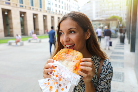 Happy young business woman eating a small pizza in her short lunch break. Urban girl eating traditional italian pizza in Milan main street, Italy. Pizza lovers concept.