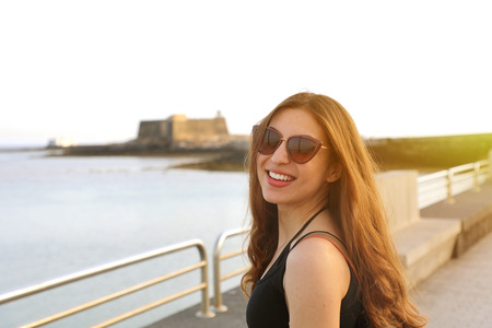 Young pretty smiling woman in black tank top and sunglasses at sunset