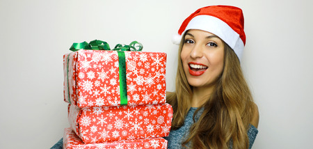 Smiling young christmas woman looking at camera with her christmas gifts on white background