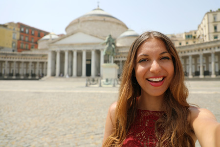 Happy smiling girl taking selfie photo in Naples with Piazza del Plebiscito square on the background, Naples, Italy