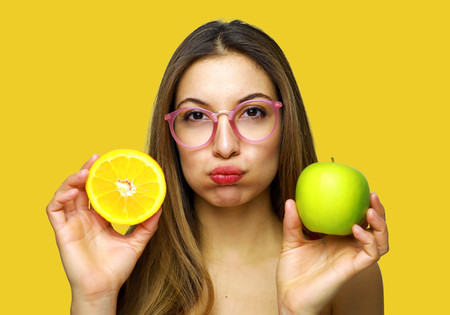 Sad woman with glasses looking at camera with healthy fruit in her hands
