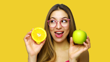 Happy funny girl presenting fruits looking to the side against orange background