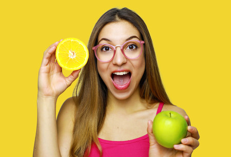 Happy cheerful laughing woman with long hair holding healthy food fruits on orange background