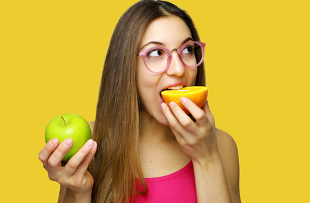 Young beautiful woman eating citrus orange fruit with apple in her hand