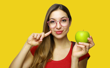 Portrait of a smiling young school nerd girl holding an apple gesturing like healthy good food isolated over yellow background