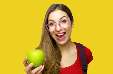 Portrait of a smiling nerd happy girl with glasses and green apple in her hand isolated over yellow background